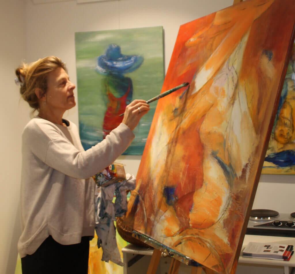 Gunhild Rasmussen maler i sit atelier og galleriet, i gang med let abstrakt og farverigt maleri